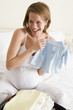 Pregnant woman packing baby clothing in suitcase smiling