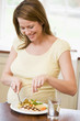 Pregnant woman in kitchen eating chicken and vegetables smiling