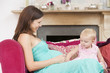 Pregnant mother with daughter in living room touching belly and