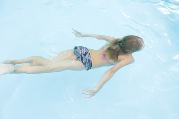 Young girl in swimming pool underwater