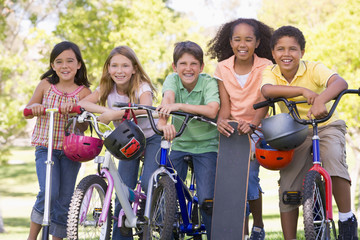 Five young friends with bicycles scooters and skateboard outdoor