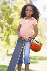 Young girl with skateboard outdoors smiling
