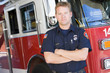 Portrait of a firefighter by a fire engine - 8652732