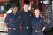 Portrait of firefighters standing by a fire engine - 8652746