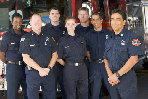 Portrait of firefighters standing by a fire engine - 8652759