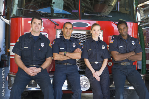 Portrait of firefighters standing by a fire engine - 8652763