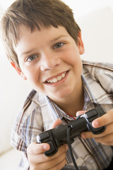 Young boy holding video game controller smiling