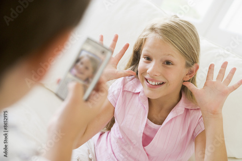 Young boy taking picture of smiling young girl with camera phone