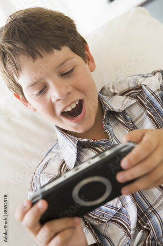 Young boy with handheld game indoors