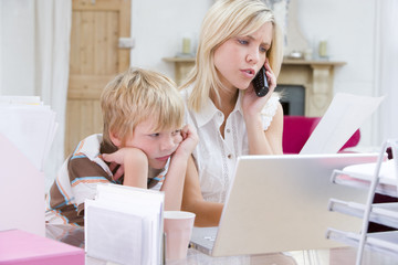 Woman using telephone in home office with laptop while young boy