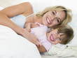 Woman and young girl in bed smiling