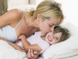 Woman kissing young girl in bed smiling