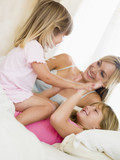 Woman and two young girls in bed playing and smiling