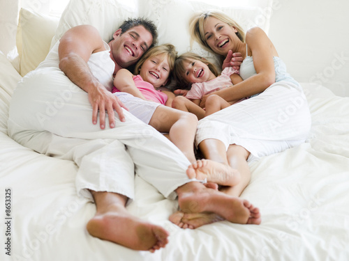 canvas print picture Family lying in bed smiling
