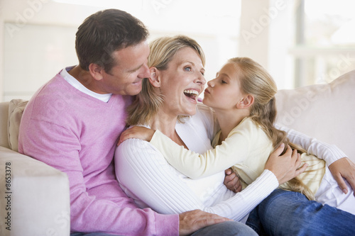 Family in living room with young girl kissing woman
