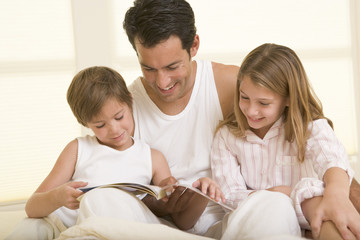 Man with two young children sitting in bed reading a book and sm
