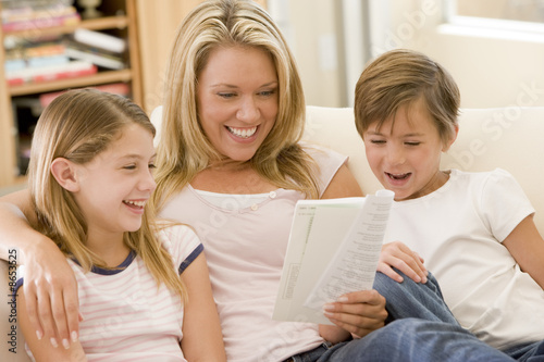 Woman and two young children in living room reading book and smi