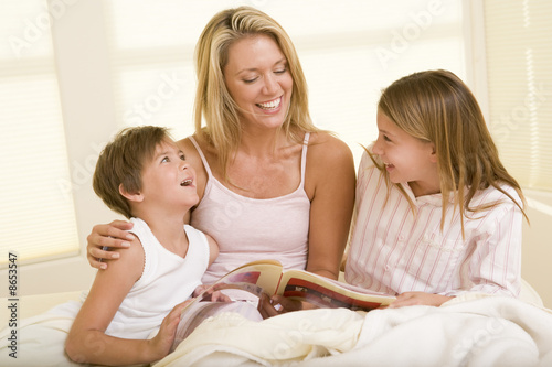 Woman with two young children sitting in bed reading book and sm