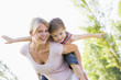 Woman giving young girl piggyback ride outdoors smiling