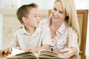 Woman and young boy reading book in dining room smiling