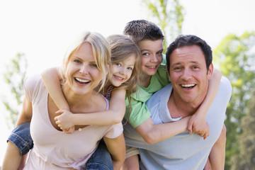 para podając dwa młode dzieci piggyback przejażdżki uśmiecha się