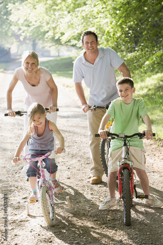 Rodzina na rowerach na ścieżce uśmiechający się