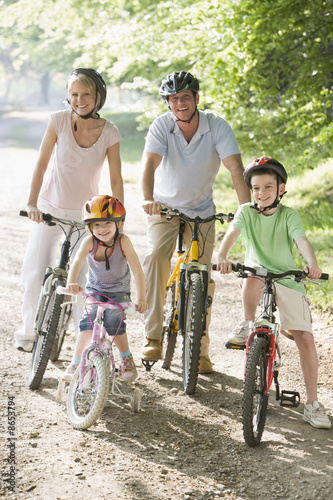 Poster Family sitting on bikes on path smiling