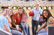 Family in bowling alley with two friends smiling