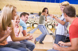 Family in bowling alley with two friends cheering and smiling