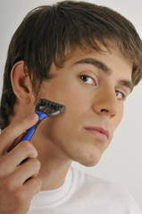Young male adult shaving face with razor