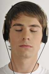 """Young male adult;listening to music with earphones"""
