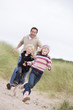 Father and two young children running at beach smiling