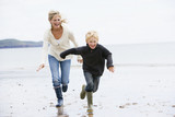 Fototapety Mother and son running on beach