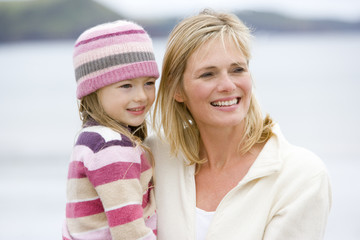 Mother holding daughter at beach smiling