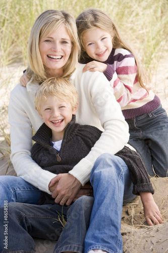 Mother and two young children sitting on beach smiling