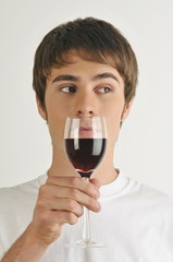 Young male adult smelling a glass of red wine