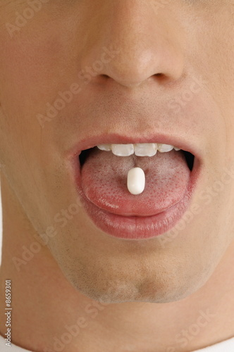 Young male adult's mouth with pill on tongue