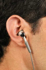 Young male adult's ear with earphone