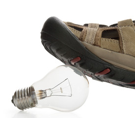 Man shoe steeping and crushing the bulb, side view