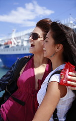 Two young women in front of ferry laughing