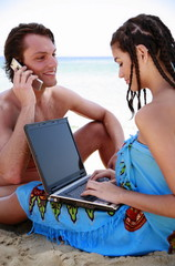 Young couple on beach with laptop and cell phone