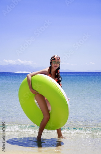 Young woman on beach with inflatable life ring