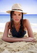 Young woman lying on beach with hat