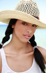Closeup of young woman on beach with hat