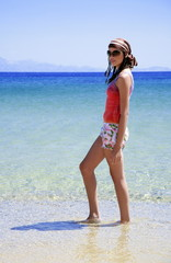 Young woman walking in the water on beach