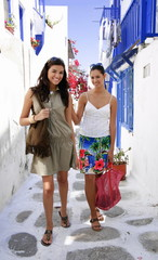 Two young women walking in alleyway
