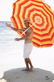 Man marching on beach with beach umbrella