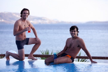 Two men with cocktails by the poolside