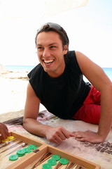 Young man on beach playing backgammon