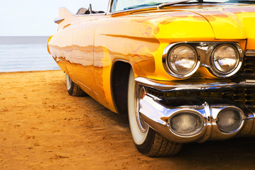 Classic yellow flame painted Cadillac at beach